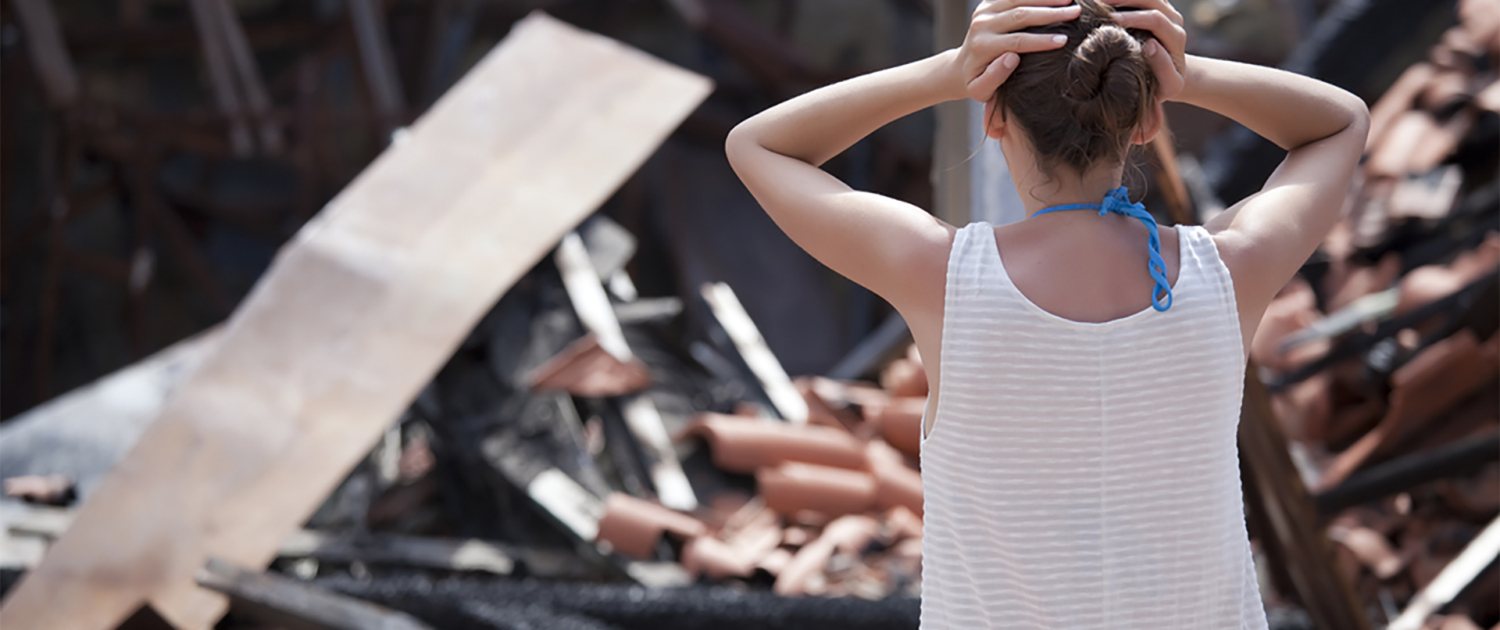 Destroyed house and sad woman