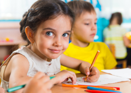 Group of preschool kids drawing with colorful pencils