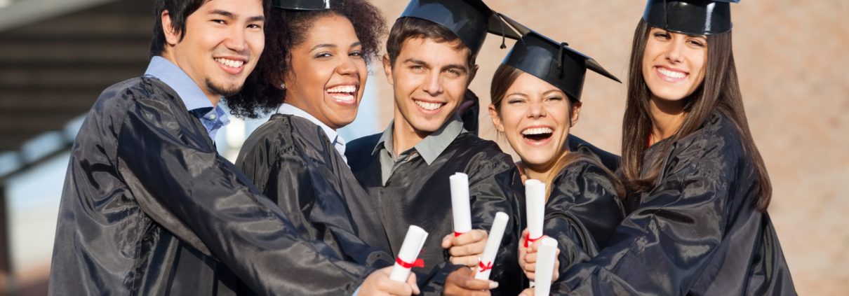 Portrait of happy students in graduation gowns showing diplomas on university campus