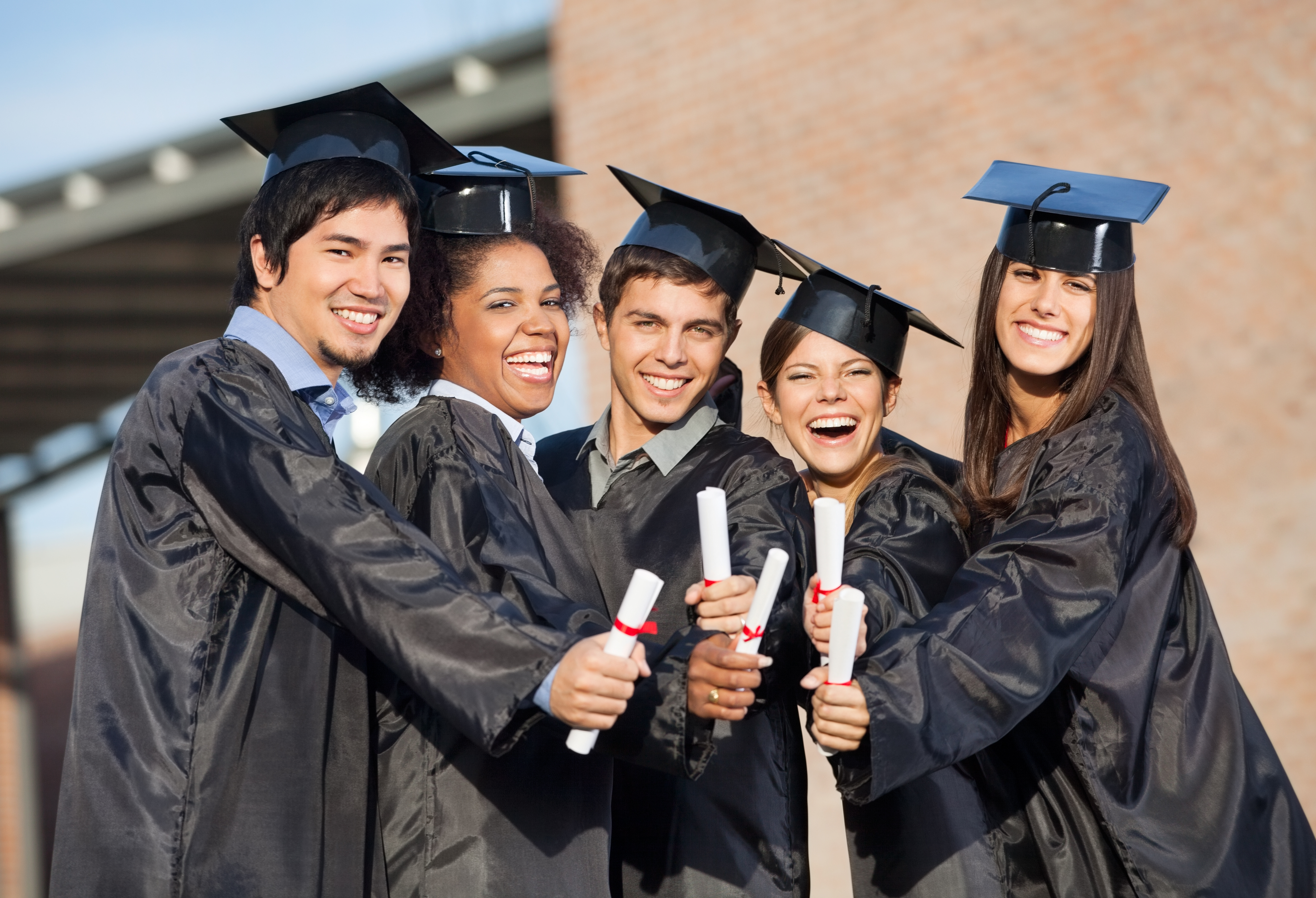 Students In Graduation Gowns Showing Diplomas On Campus - Federal ...