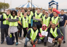a group of young people in safety yellow vests posing in front of a carousel and playground at the 2017 public service 5k
