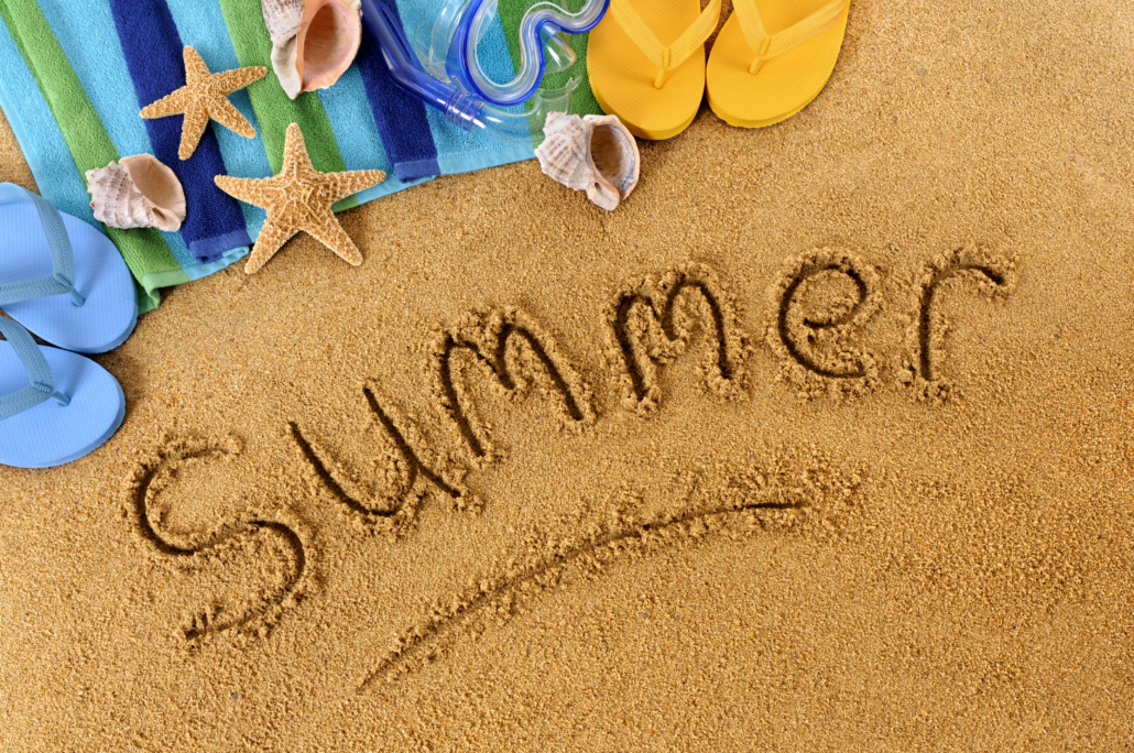 The word Summer written on a sandy beach, with scuba mask, beach towel, starfish and flip flops