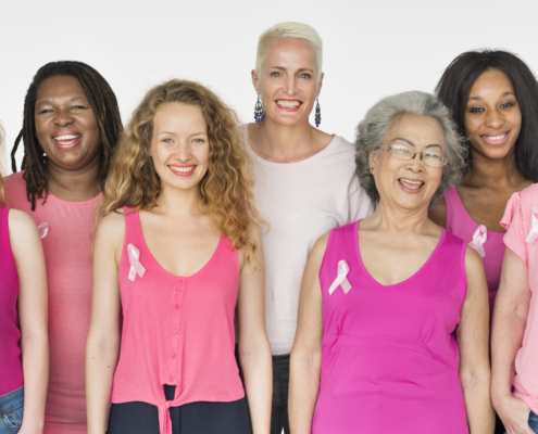 diverse group of women wearing pink shirts with awareness ribbons