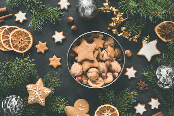 a tin of holiday cookies surrounded by silver decorations and pine boughs