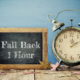 an old fashioned clock sits next to a chalkboard saying fall back 1 hour