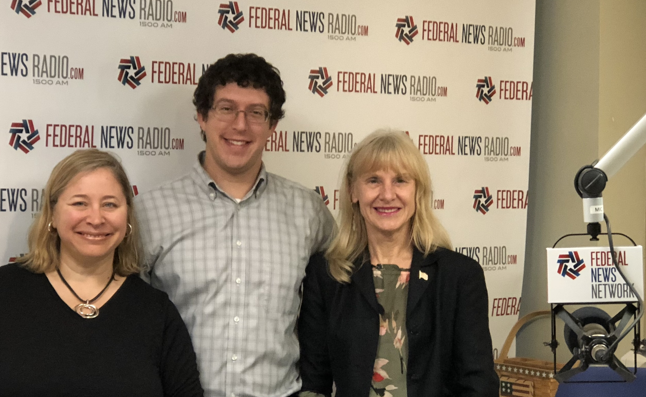photo of FEEA's Joyce Warner, FEDTALK Host Jason Briefel, and Long Term Care Partners' Joan Melanson in front of federal news network step and repeat