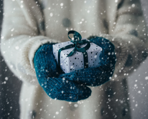 a person wearing a cream winter sweater and blue mittens holding a small gift wrapped in white paper and blue ribbon in outstretched hands. it is snowing