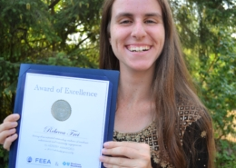 a photo of scholarship winner rebecca holding her feea scholarship certificate