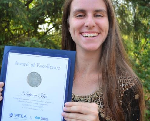 a photo of scholarship winner rebecca holding her feea scholarship certificate
