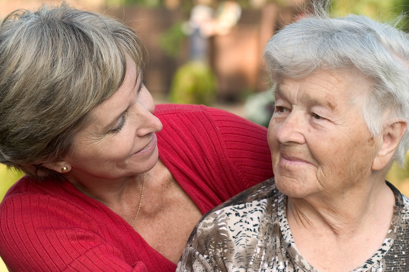 a daughter embraces her elderly mother