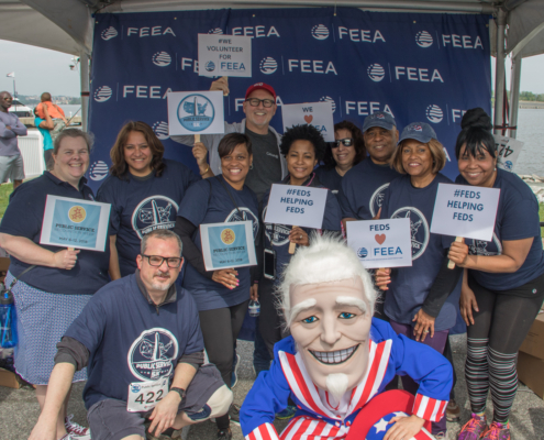 race participants holding signs in support of public service pose with Uncle Sam in front of FEEA logo