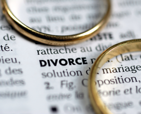 two gold wedding rings laying on a dictionary page with the definition of divorce