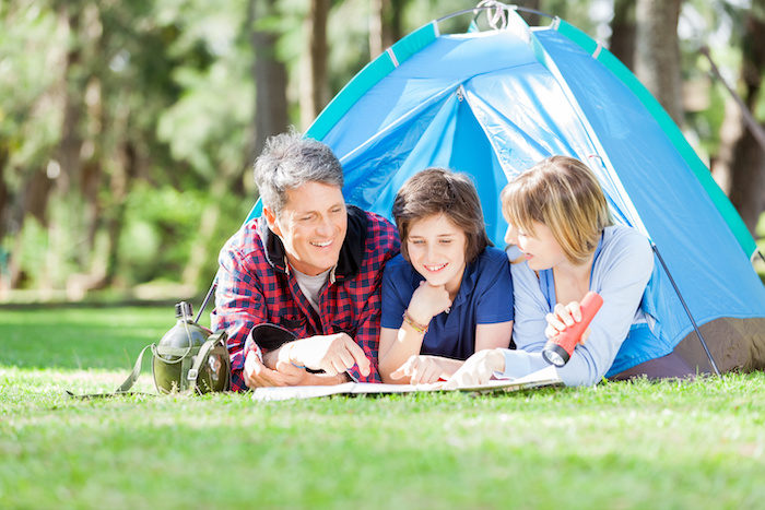Family Studying Map While Lying In Tent