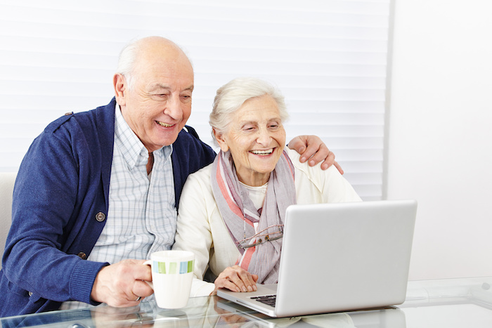 an older couple chats with family via laptop