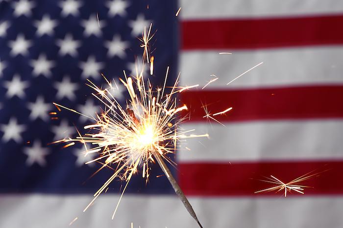 Sparkler against USA flag. Independence Day celebration