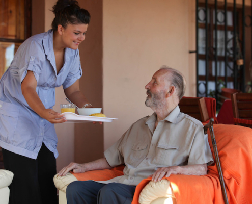 nurse or helper in residential home giving food to senior man
