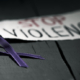 a purple ribbon for the awareness about the unacceptability of the violence against women and the text stop violence on a piece of paper, on a dark gray rustic wooden surface