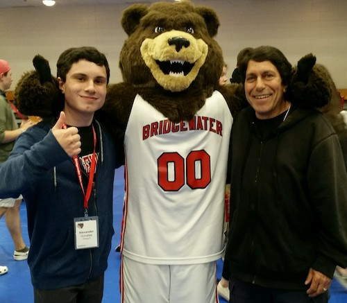 a college student gives a thumbs up with right hand while left arm is around his college mascot, a bear in a basketball uniform, his father stands on the other side of the mascot