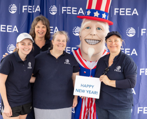 FEEA staff Alyssa, Niki, Robyn, and Joyce wearing dark blue polo shirts with FEEA logos stand with a person in Uncle Sam costume with red, white, and blue tophat in front of a blue step-and-repeat of the FEEA logo holding a Happy New Year sign