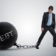 Young businessman has chained big metal ball to his leg with debt