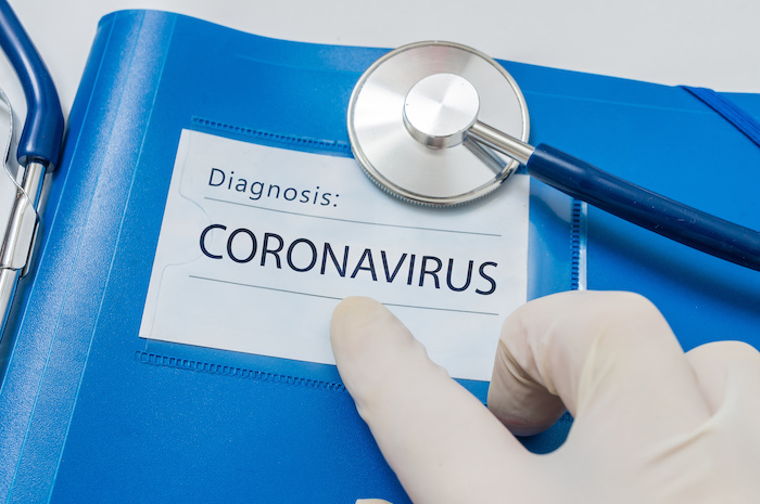 a gloved hand points at the words diagnosis coronavirus
