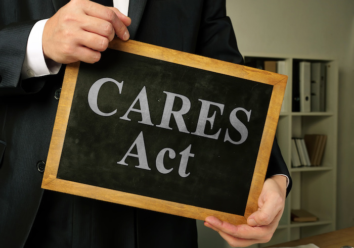 a man holds a small chalkboard with the words CARES Act on it