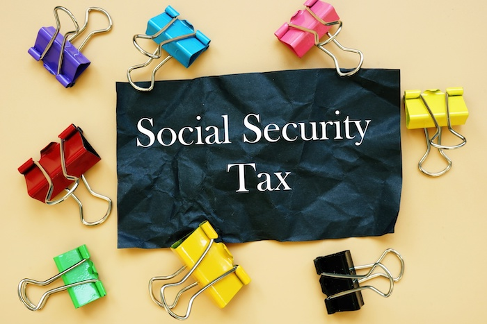 The photo says Social Security Tax. Notepad, pen, marker.