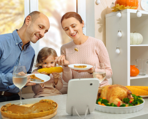 A happy family have a thanksgiving dinner and sends a video greeting to their parents .