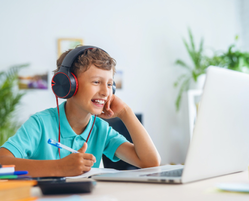 cheerful boy with headphones uses laptop for online school