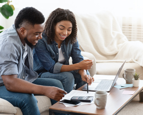 Smiling Black Couple Discussing Finances At Home