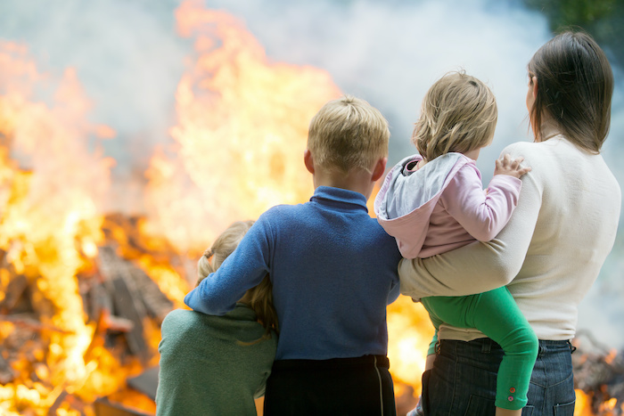 Family mother with children at burning house background
