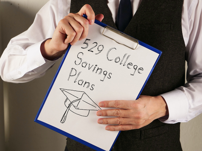 529 College Savings Plans is shown written on a page on a clipboard held by the hands of a person whose face is not in the frame