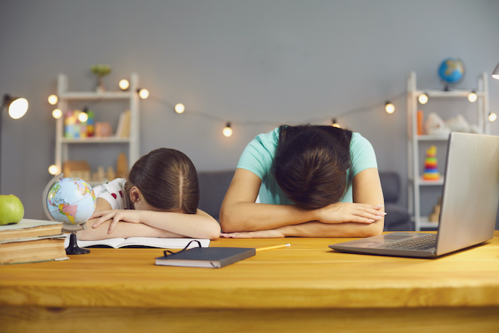 Little girl with her mother lying on table near laptop computer, exhausted from online home schooling