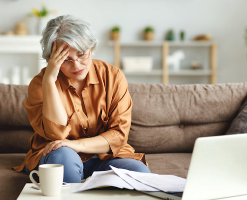 stressed woman with hand to forehead looking at financial papers and computer