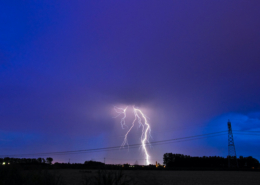 a lighning storm over a town at night
